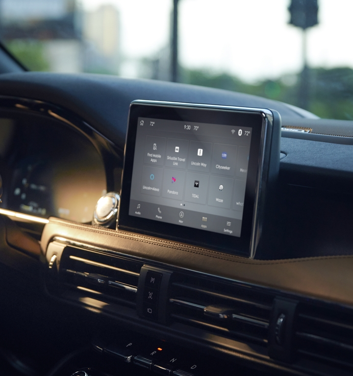 The center screen inside a 2020 Lincoln Corsair is displaying the simple SYNC 3 interface as sunlight and shadows highlight details of the dash