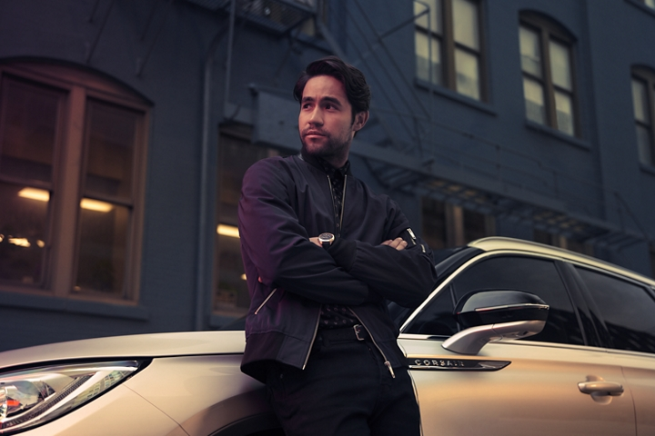 A musician is leaning against a 2020 Lincoln Corsair parked in front of a blue brick building as fading daylight plays on the curves of the exterior