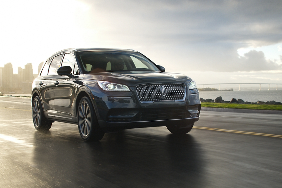 A 2020 Lincoln Corsair in flight blue is being driven along a coast with active power and precision