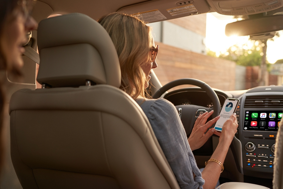A woman is shown sitting in the drivers seat of a Lincoln M K C as she downloads an app on her mobile phone.