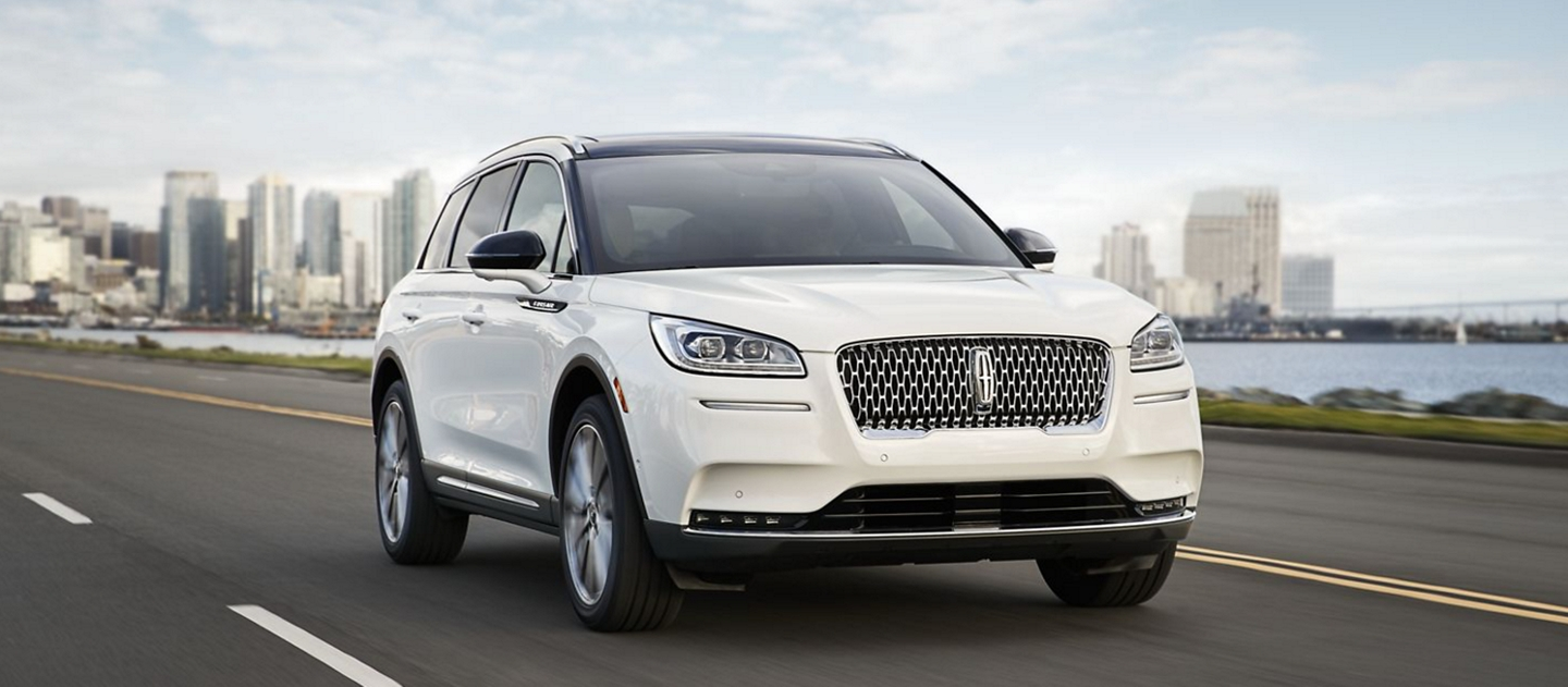 A Lincoln Corsair in pristine white is effortlessly driving along a coast using Lincoln Drive modes.