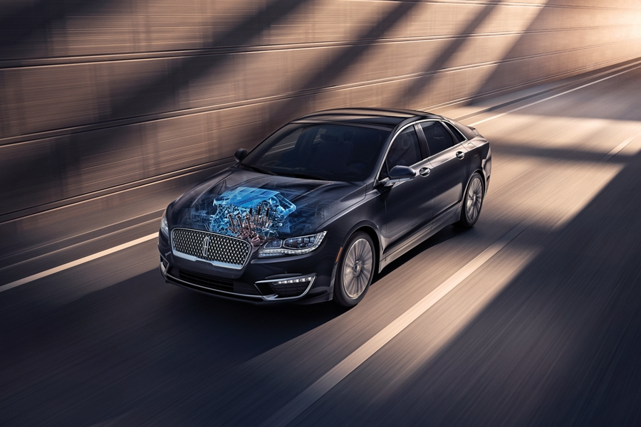 An illustration of the three liter engine is overlaid upon a photograph of a 2020 Lincoln M K Z while it is being driven