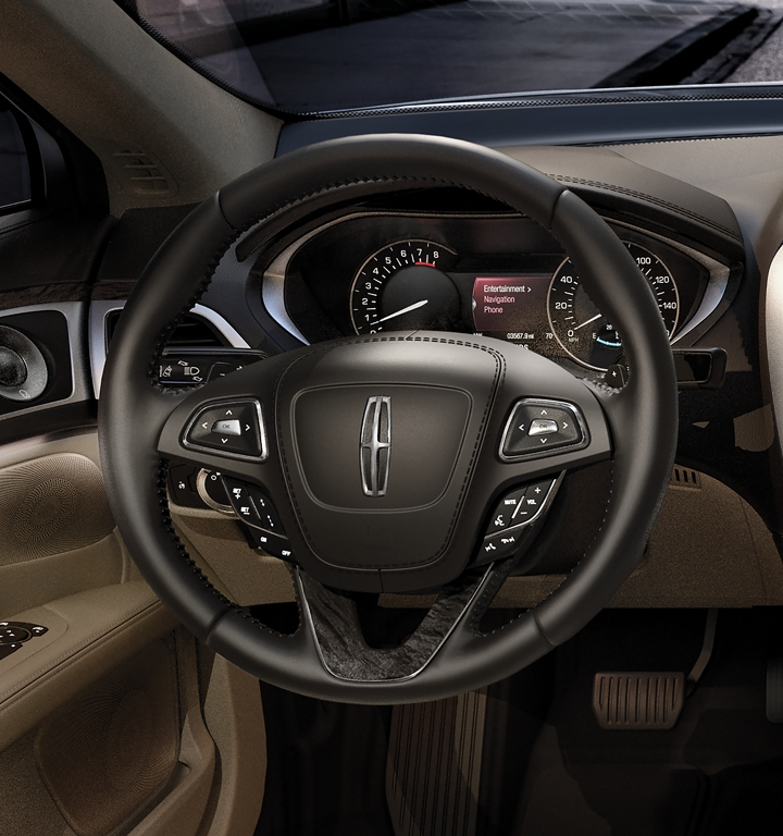 The leather wrapped steering wheel in the 2020 Lincoln M K Z is shown with sunlight bouncing off the in wheel controls