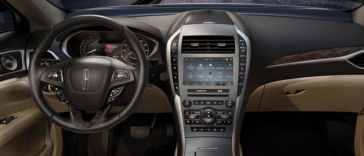 A touch screen is shown in the center of the dash with various entertainment options shown