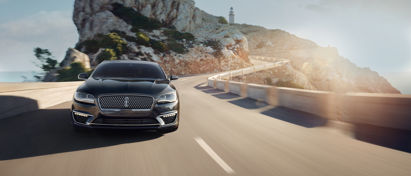 The sun wraps the 2020 Lincoln M K Z in light as it is shown being driven along a seaside road