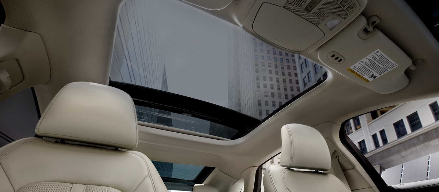 Towering city skyscrapers are shown through the open glass roof of a 2020 Lincoln M K Z