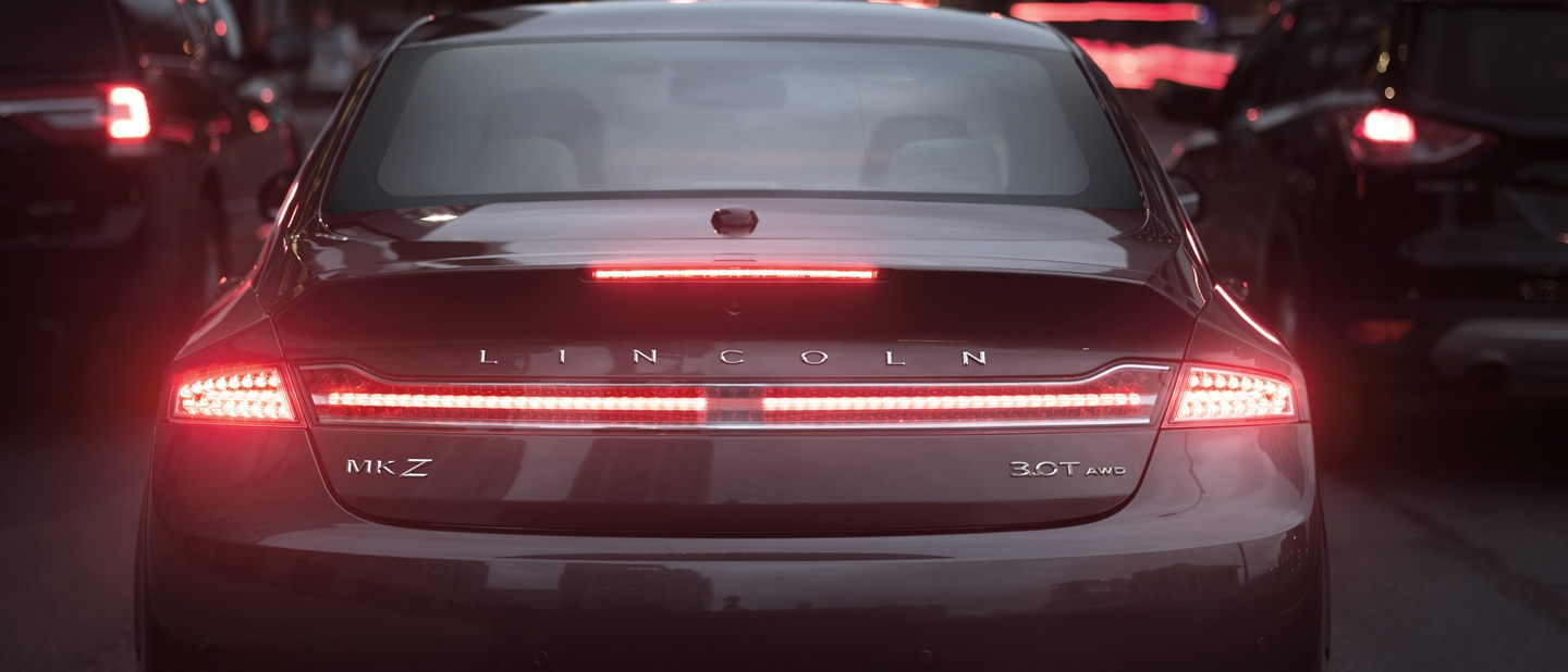A 2020 Lincoln M K Z is shown with its brake light illuminated to demonstrate emergency braking