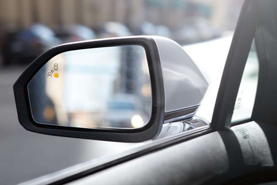 Warning lights are displayed in the drivers side view mirror indicating something is in the vehicles blind spot