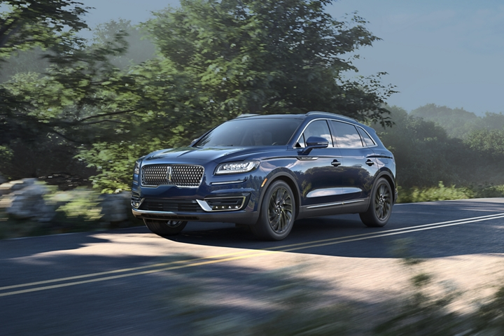 A 2020 Lincoln Nautilus shown in the rhapsody blue color is being driven down a country road