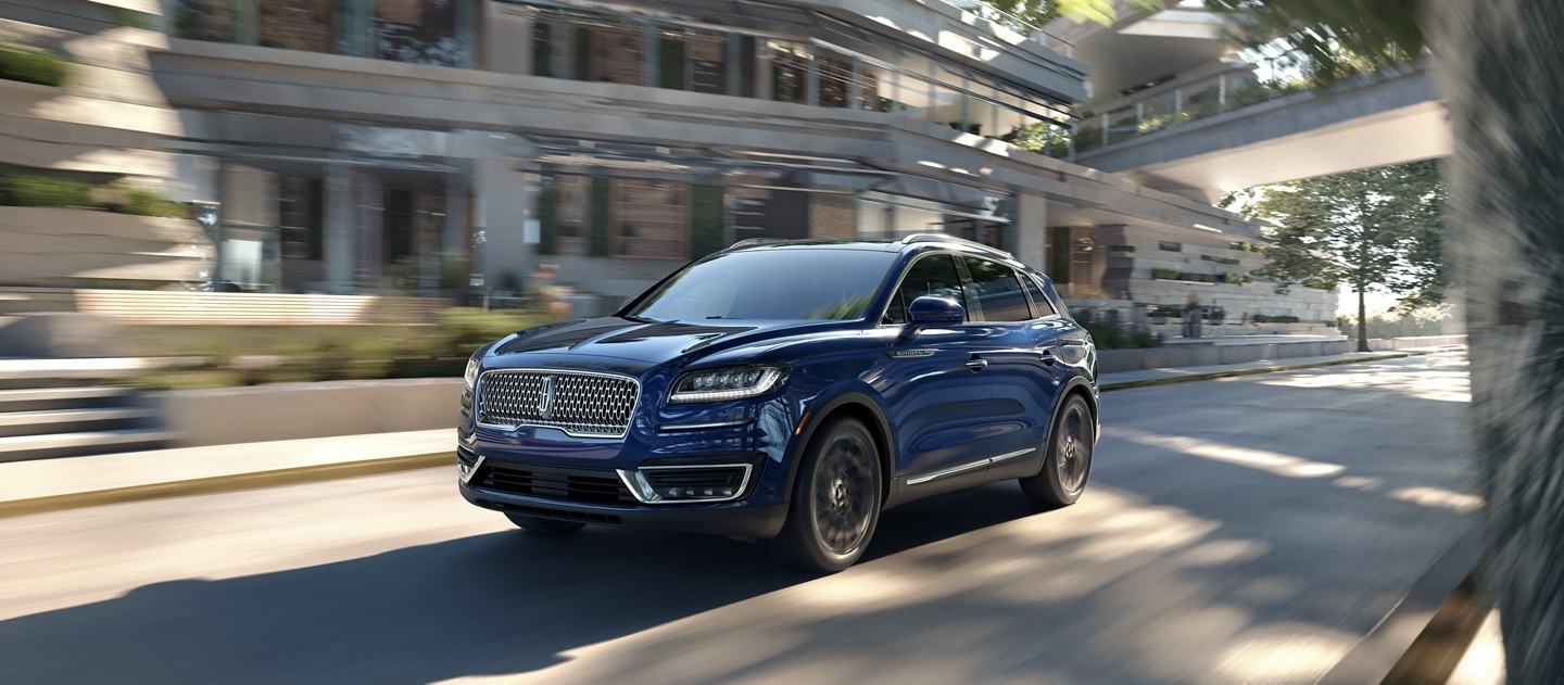 A 2020 Lincoln Nautilus in the Rhapsody Blue exterior color is shown being driven into a city