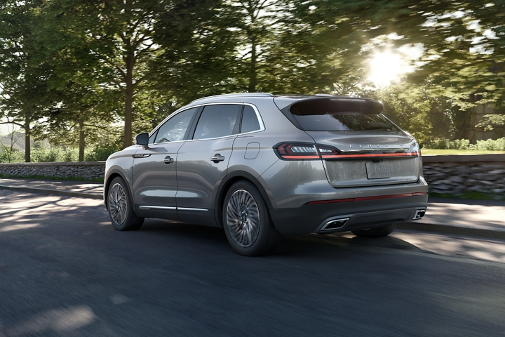 A 2020 Lincoln Nautilus is shown being driven along a scenic tree lined road to demonstrate adaptive cruise control