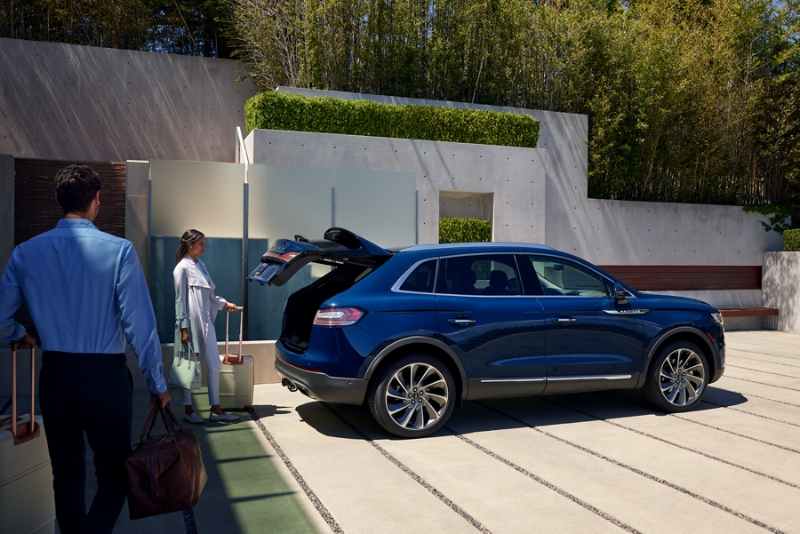 The hands free power liftgate is shown as it is opening while a couple prepare to load baggage into the rear cargo area