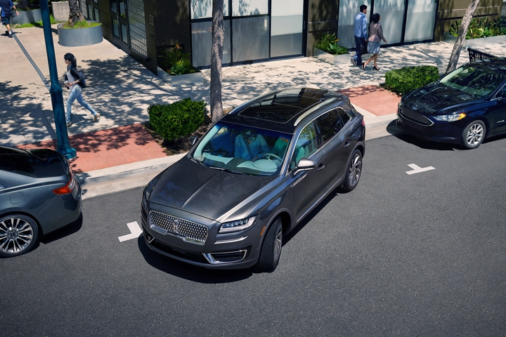 A 2020 Lincoln Nautilus is shown being parallel parked courtesy of available enhanced active park assist