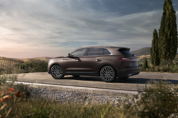 A 2020 Lincoln Nautilus shown in the Ochre Brown exterior color is shown parked at a scenic country overlook
