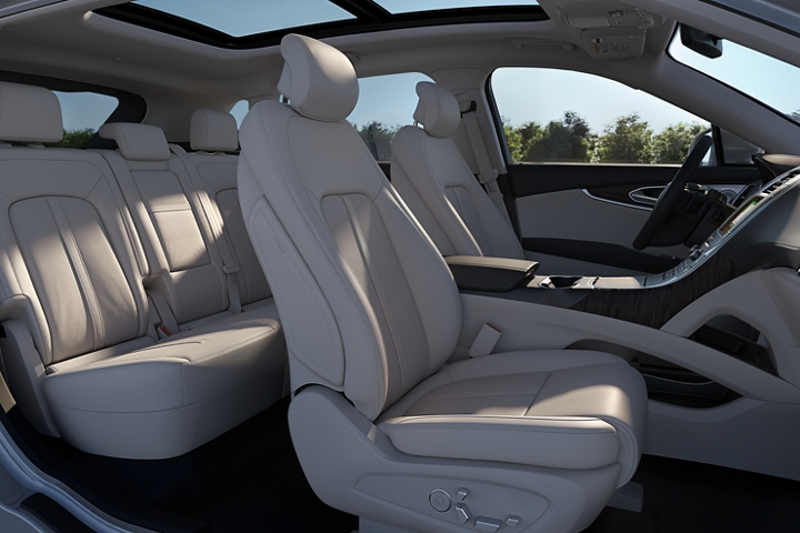 A passenger side view of the front cabin of a 2020 Lincoln Nautilus seen in the Cappuccino interior color