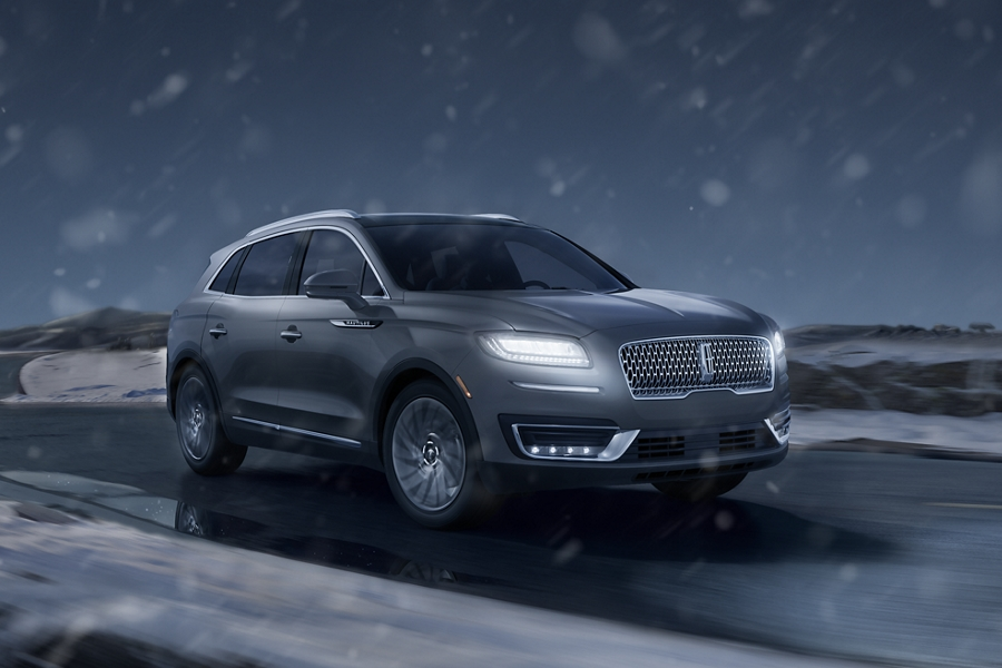 Falling snow catches the beams of the headlamps of a 2020 Lincoln Nautilus as it is driven on a snowy road