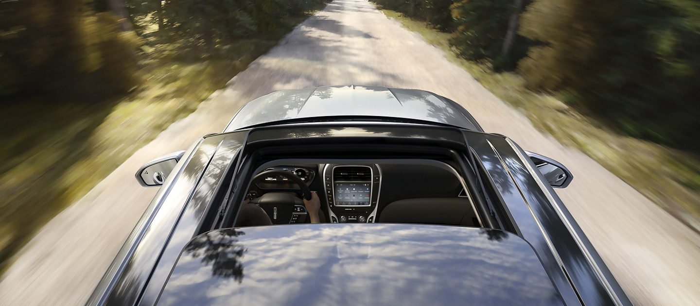 A 2020 Lincoln Nautilus is shown being driven along a country road with its available panoramic Vista Roof open