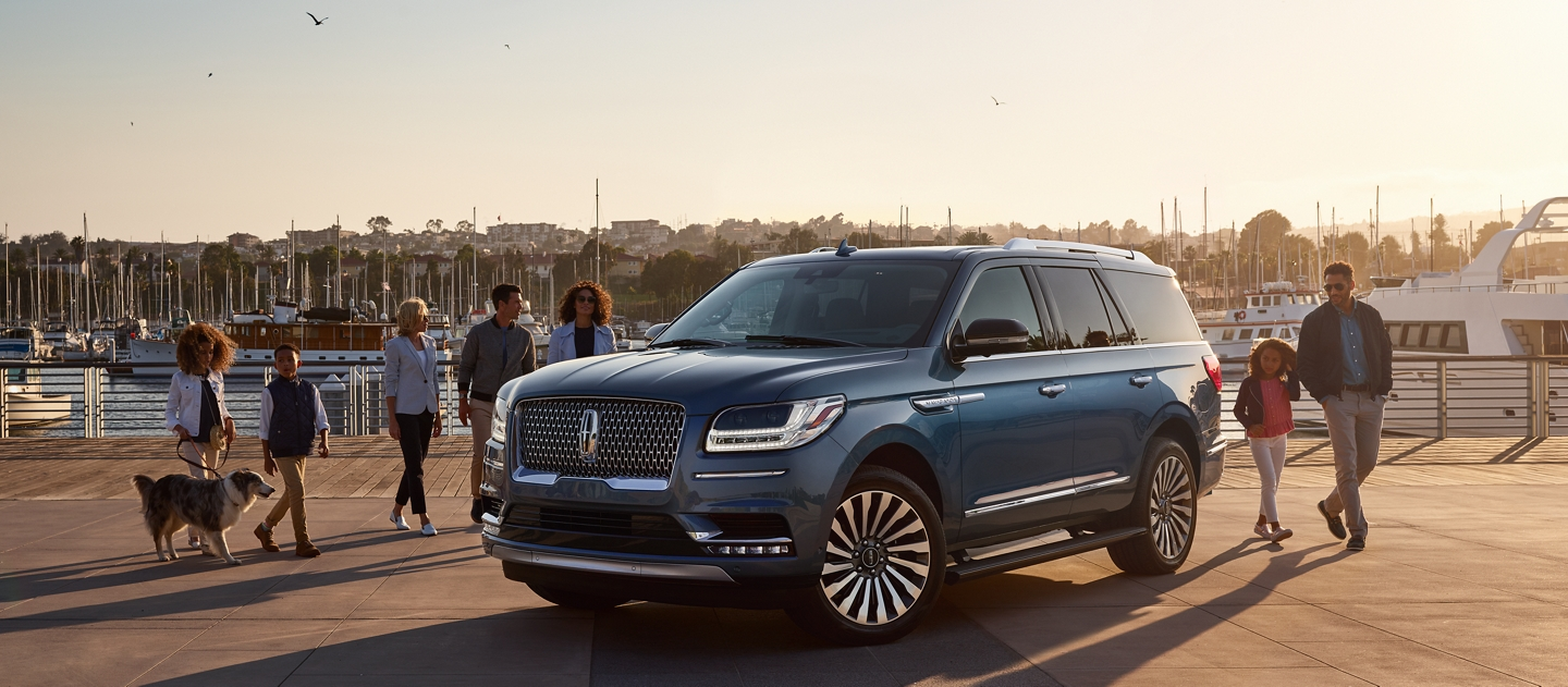 Family and friends with a dog approach a 2020 Lincoln Navigator parked at a marina as the setting sun casts long dramatic shadows from their forms