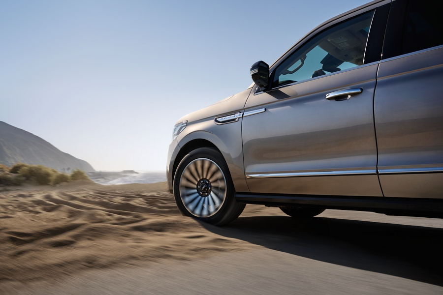 A 2020 Lincoln Navigator with available four wheel drive is being driven through sunny sandy terrain creating shadows that mimic waves in the sand