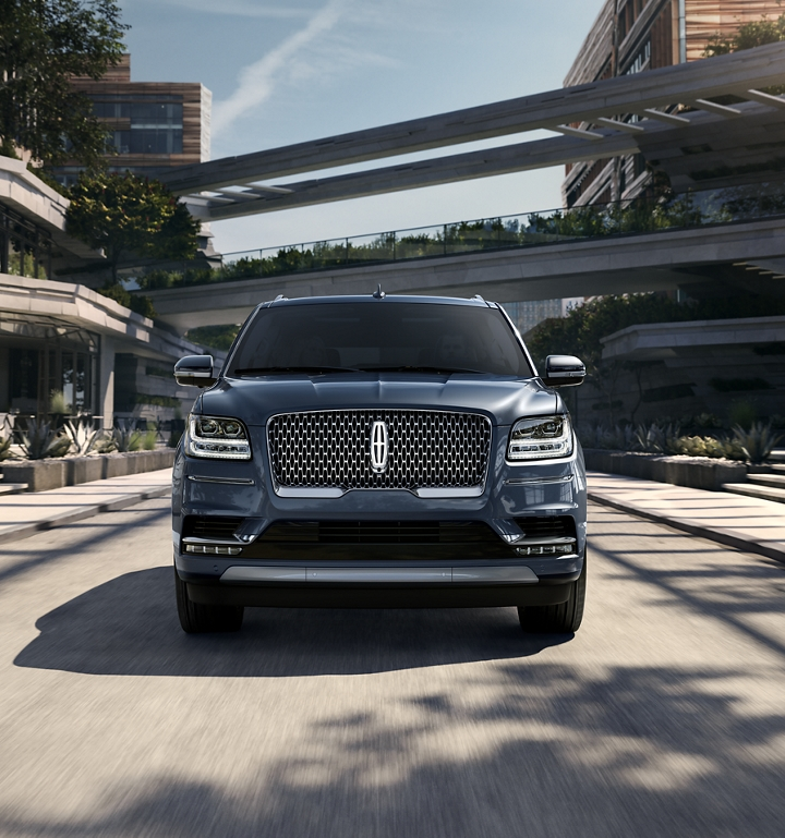 A Lincoln Star glows with available illumination on the grille of a 2020 Lincoln Navigator that is being driven under overpasses