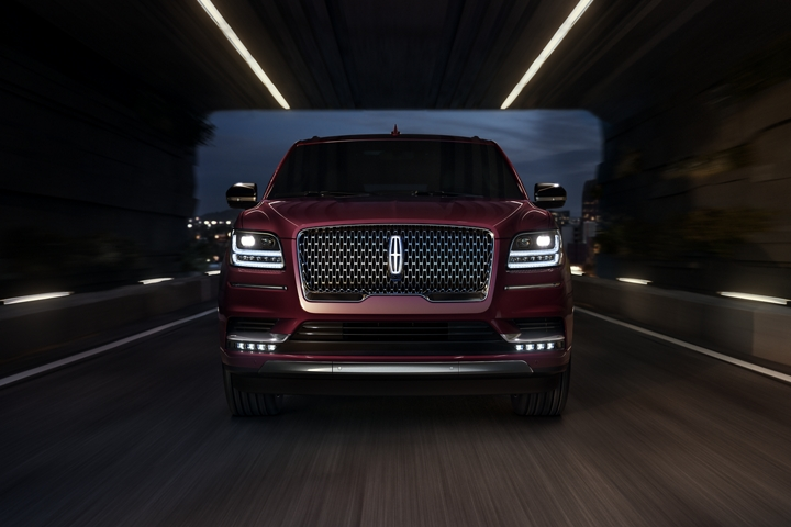 A 2020 Lincoln Navigator is being driven through a dark tunnel showing the available illuminated Lincoln star in the grille as a beacon in the night