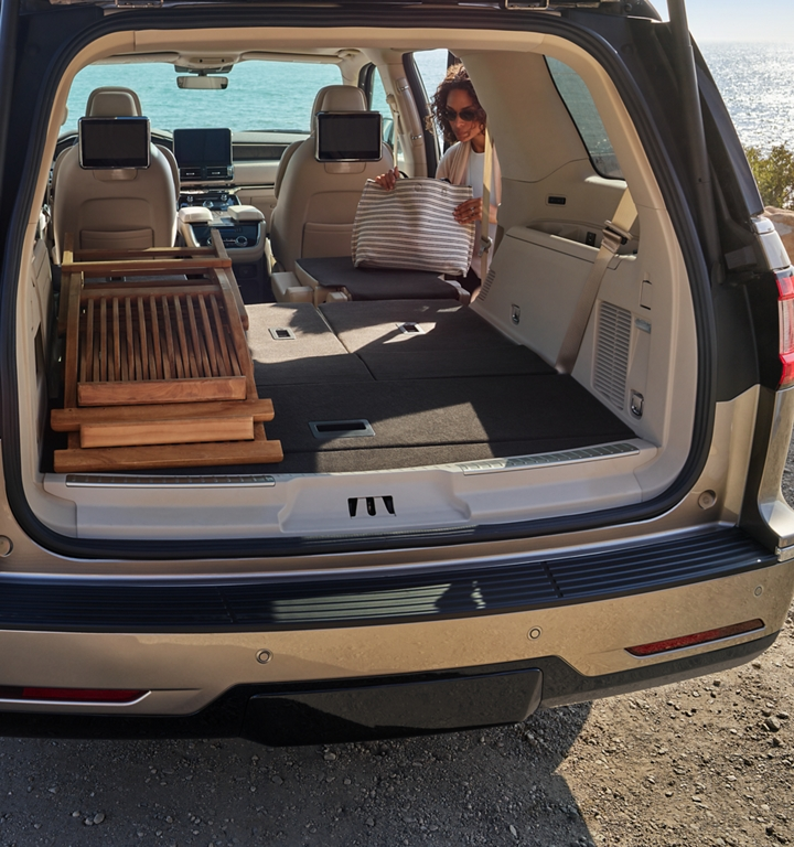 The second and third rows of a 2020 Lincoln Navigator are folded flat to show cargo space as a mother unloads a bag at a beach with sparkling waters