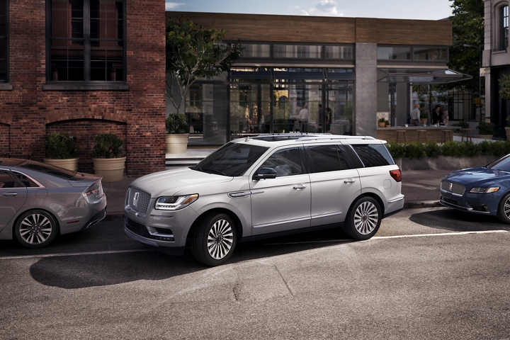 A 2020 Lincoln Navigator is shown being parallel parked outside a modern outdoor cafe downtown to demonstrate enhanced active park assist