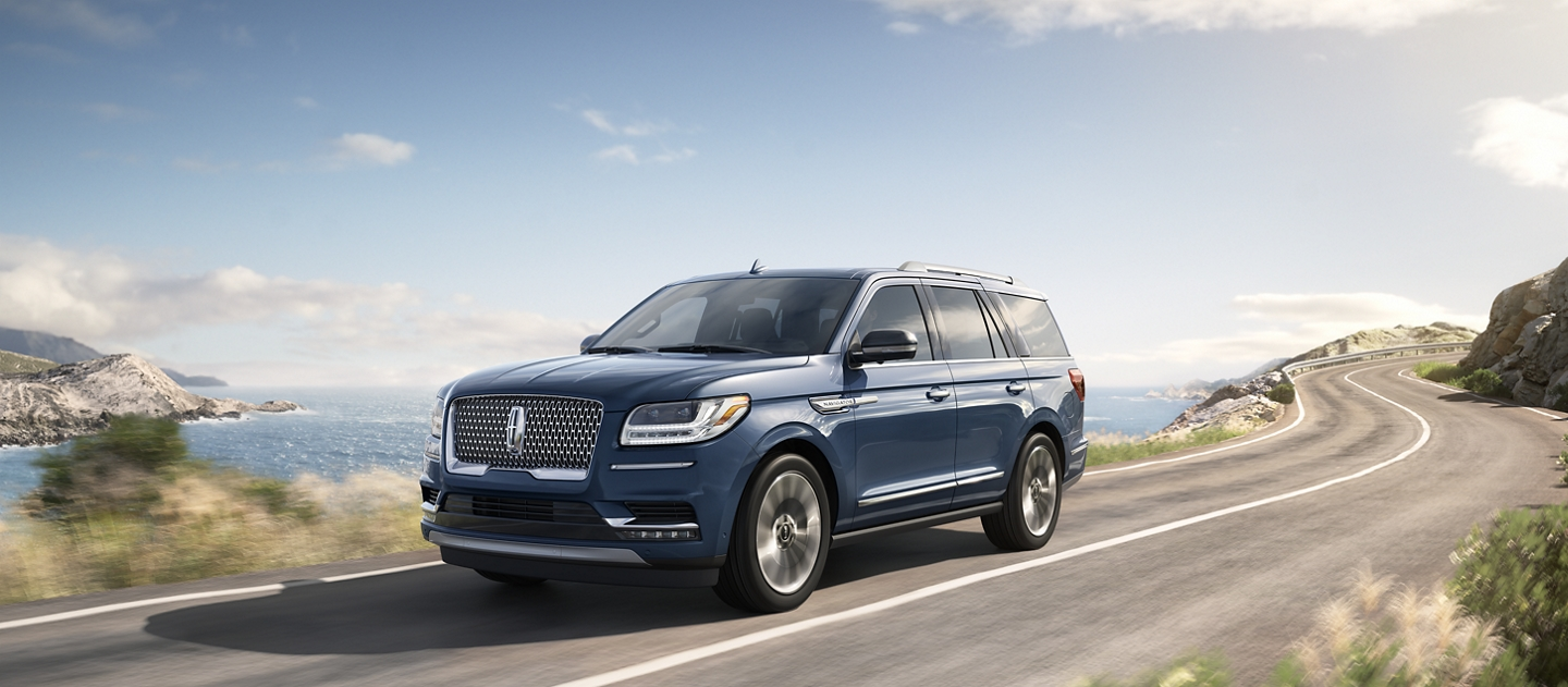 A 2020 Lincoln Navigator in Blue Diamond is being driven down the sloping coast of a sunny sea side destination