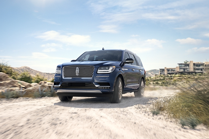 A 2020 Lincoln Navigator in Rhapsody Blue is being driven away from a contemporary beachside resort around a sharp turn on a sandy road