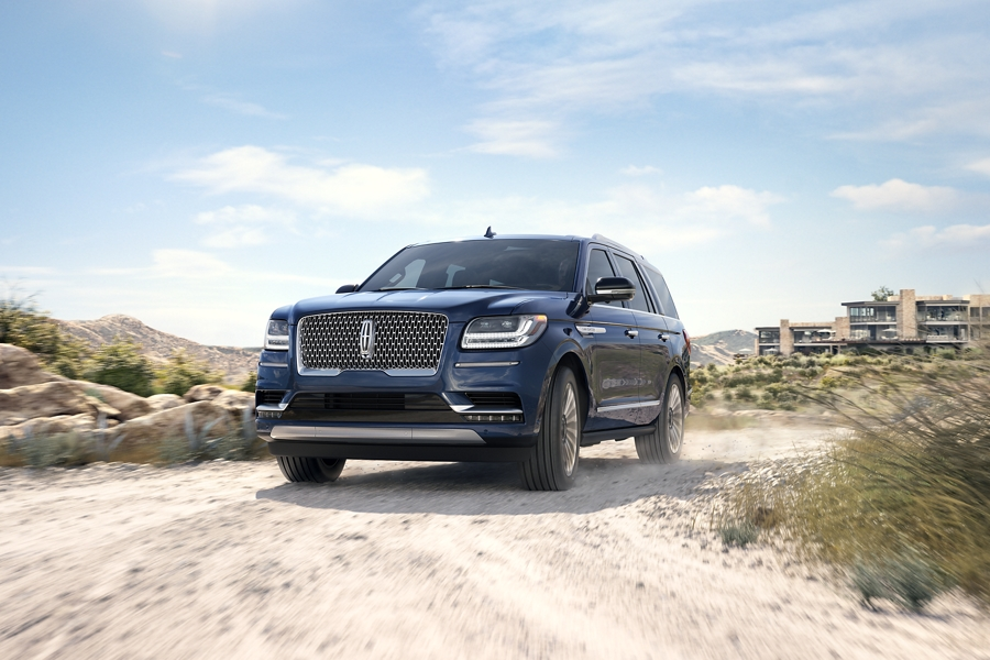 A 2020 Lincoln Navigator in Rhapsody Blue is being driven away from a beach side resort around a sharp turn on a sandy road