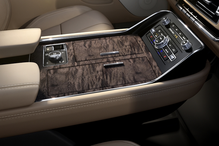 Deep polished wood featuring natural grain patterns adorns the spacious three chambered center front console design with ample storage