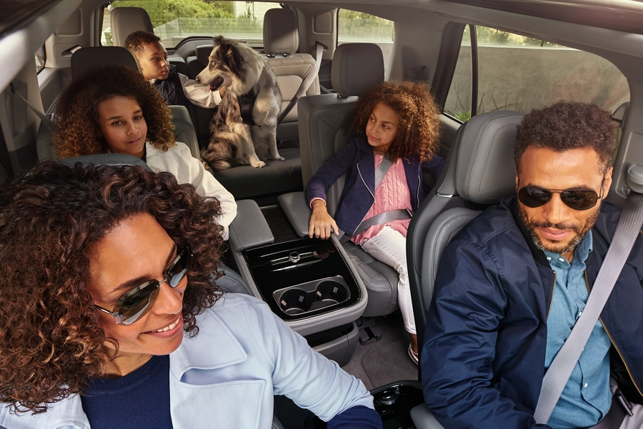 A family of five and their dog look out the window at scenery and enjoy the spacious comfort and open airiness of the 2020 Lincoln Navigator interior