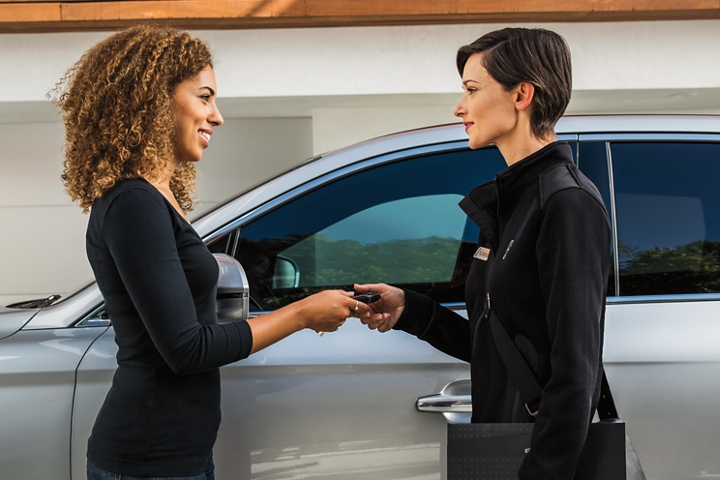 A woman is handing her key to a female Lincoln representative in front of a 2020 Lincoln Navigator for Pickup and Delivery