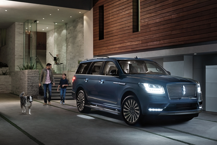 A father son and dog walk up to a 2020 Lincoln Navigator illuminated by the Lincoln Embrace lights at night