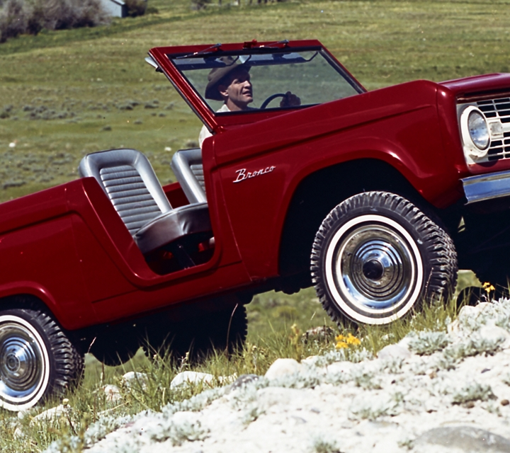 a classic ford bronco is shown driving up a rocky hill