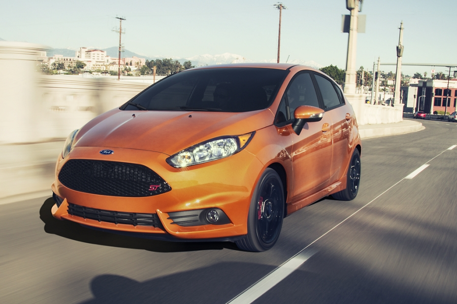 Three quarters shot of a Ford Fiesta G T in Orange Spice driving down a city road