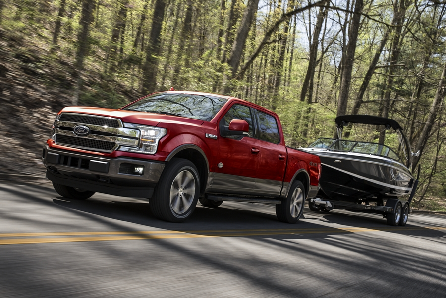 Front three quarter view of a Ford F 1 50 towing a boat on a wilderness highway