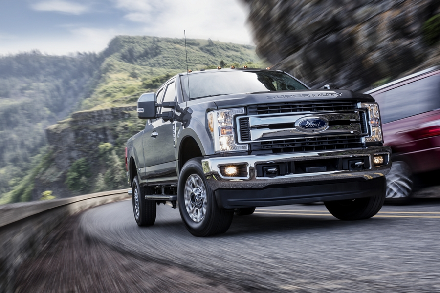 Front view of a 2019 Ford F 1 50 Lariat in Chrome driving under a freeway overpass