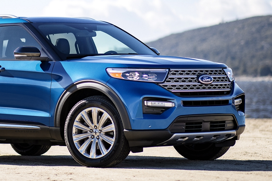 Three quarter view of a Ford Explorer Hybrid Platinum in Atlas Blue parked on the shoreline of a mountain lake