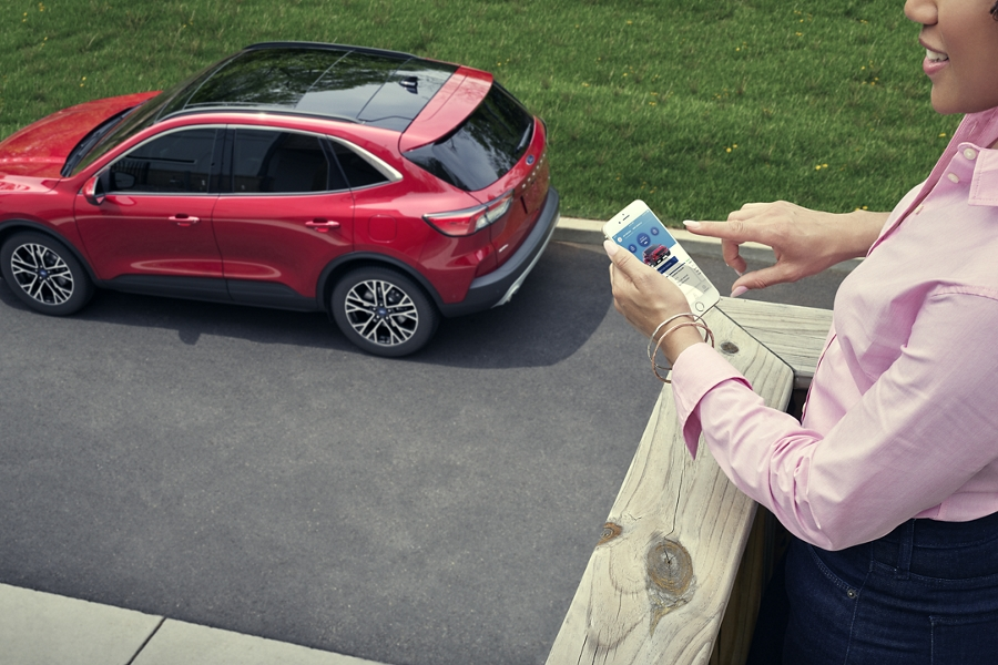 Overhead view of a woman tapping a mobile device near a parked Ford Escape Plug In Hybrid