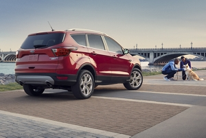 Two people petting a dog near a 2019 Ford Escape in ruby red