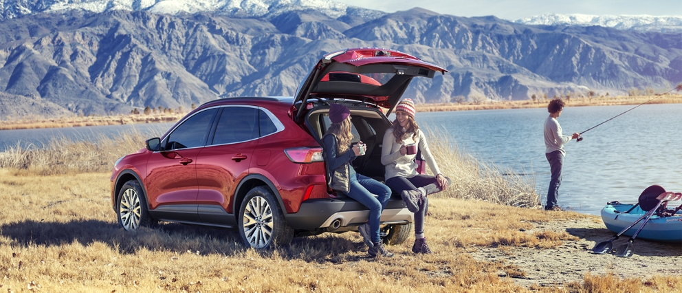 2020 Ford Escape Titanium in Rapid Red Metallic Tinted Clearcoat with an open liftgate parked by a lake