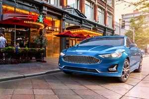 A 2020 Ford Fusion in velocity blue parked next to a restaurant