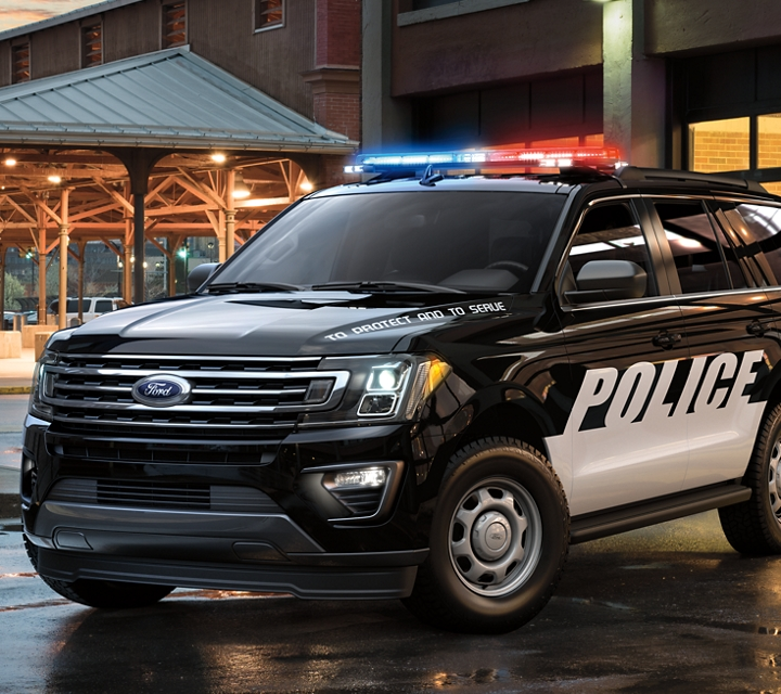The ford expedition special service vehicle in front of a city garage