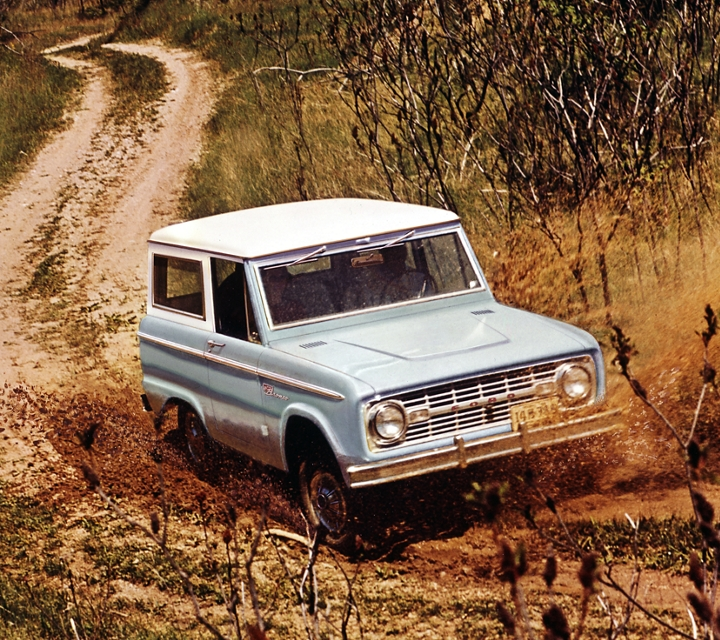 A 1967 Ford Sport Bronco Wagon being driven on a dusty trail