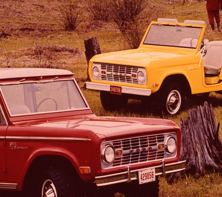 Three 1969 Ford Broncos parked in a wilderness field while a group of people walks nearby