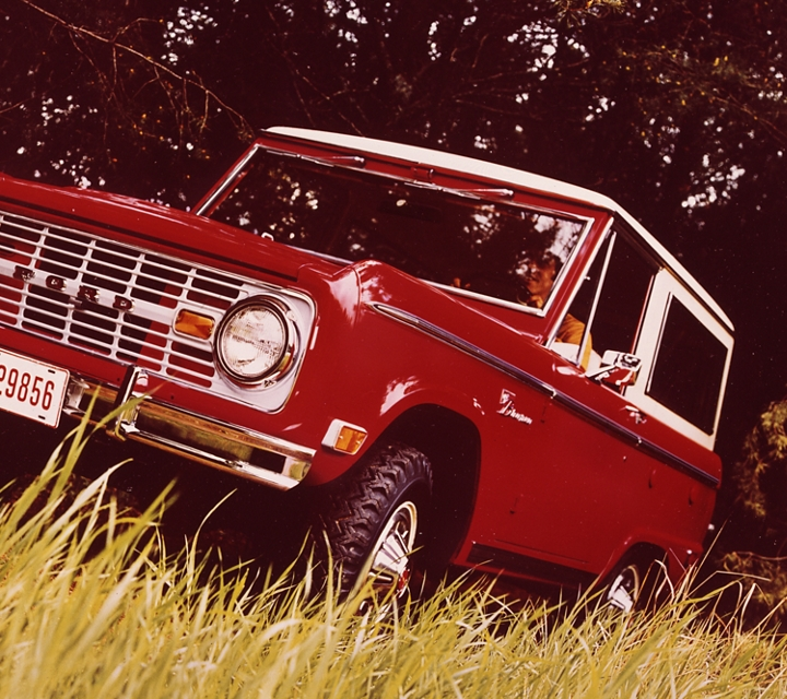 A 1969 Ford Bronco Sport Wagon in Royal Maroon with Wimbledon White roof driving through tall grass in the wilderness