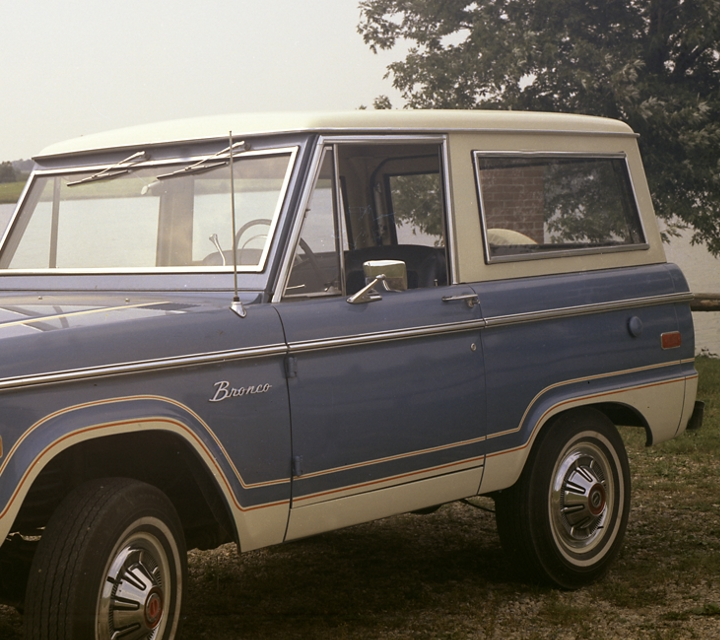 1973 Ford Bronco in Wind Blue with Wimbledon White roof with Wimbledon White rocker panels parked on grass next to a lake