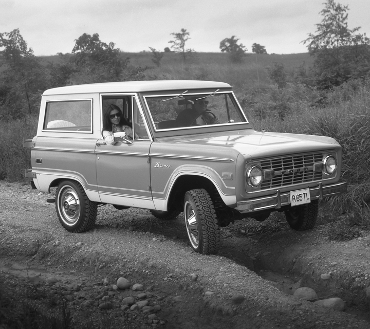 A black and white image of the 1975 Ford Bronco Ranger being driven off road