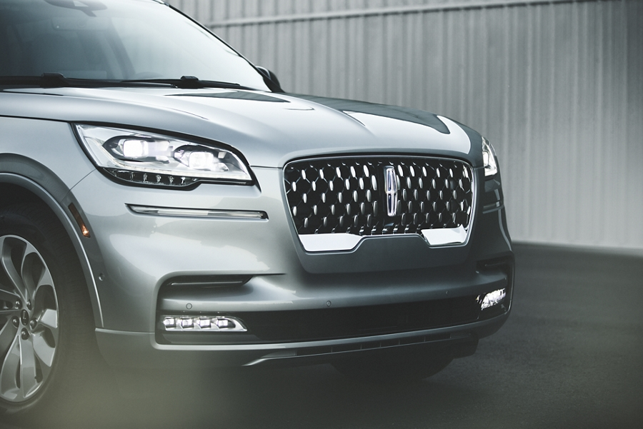 The adaptive pixel L E D headlamps of a Lincoln Aviator and the centrally located Lincoln Star logo glow with elegance